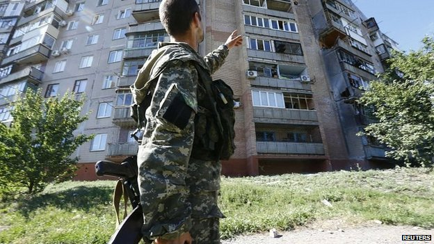 Pro-Russia fighter points to apartments damaged by shelling in Sloviansk, Ukraine. 29 June 2014