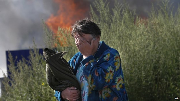 Woman cries after shelling set light to her house in Sloviansk, east Ukraine. 30 June 2014