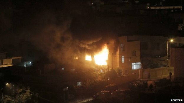 Flames and smoke are seen after a blast in the top floor of the family home of an alleged abductor in the West Bank City of Hebron, 1 July 2014