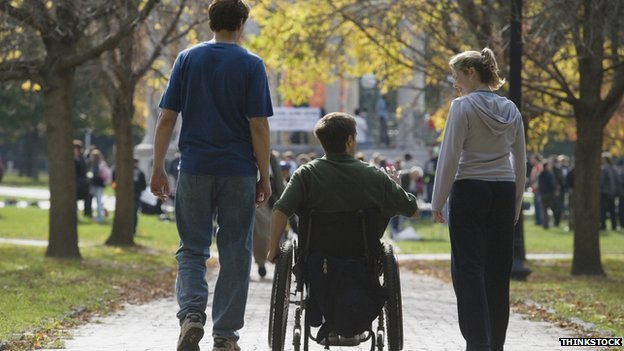 Three people walking down a path, a woman, a man in a wheelchair and another man