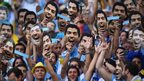 Uruguay fans hold up and wear Luis Suarez masks ahead of the World Cup match against Colombia
