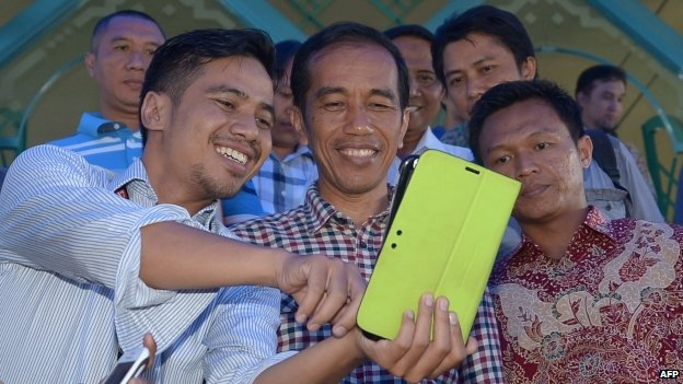 Indonesian men have their picture with presidential candidate Joko Widodo (centre) at a mosque as his entourage stops by for a prayer during his campaign in Jakarta on 30 June 2014.