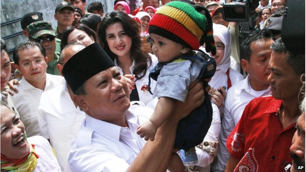 Indonesian presidential candidate Prabowo Subianto (centre) lifts a baby boy during his campaign rally in Bandung, West Java, Indonesia, on 5 June 2014.