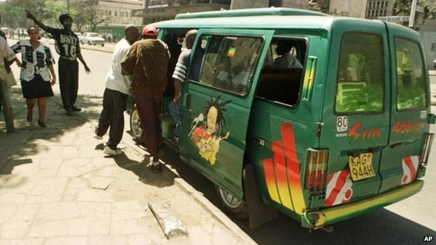Two men boarding a green painted minibus in Nairobi