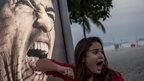 A tourist jokes in front of an advertisement featuring the portrait of Uruguay's forward Luis Suarez at Copacabana beach in Rio de Janeiro