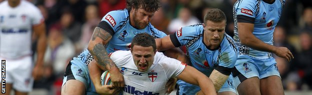 Ashton Sims (l) tackles England's Sam Burgess