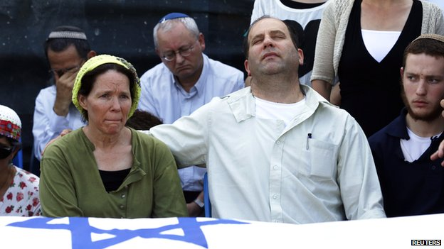 Rachel (front L) and Avi (2nd R) Frenkel, parents of US-Israeli national Naftali, 16, one of three Israeli teens who were abducted and killed in the occupied West Bank, mourn near the Israeli flag-covered body of their son during a memorial service before his funeral, in the central Israeli village of Nof Ayalon