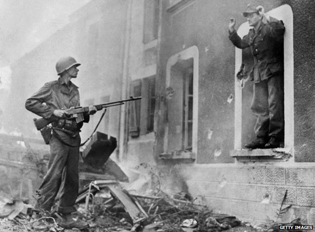 US soldier points a gun at German soldier