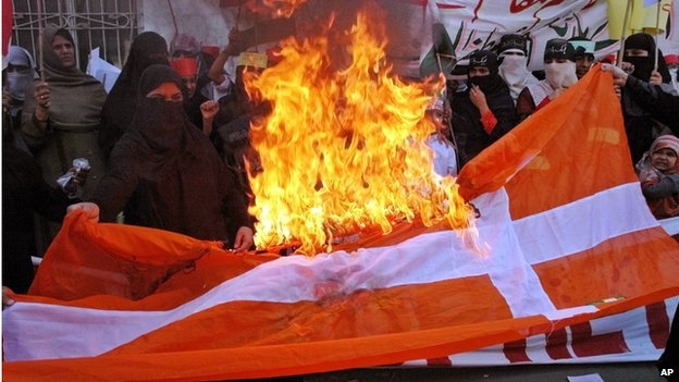 Pakistanis burn Danish flag during a rally in Lahore, Pakistan on 24 February 2006