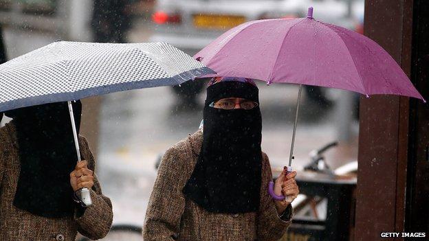 Women, sheltering under umbrellas, wear full face Niqab on the streets of Blackburn on 20 July 2010.