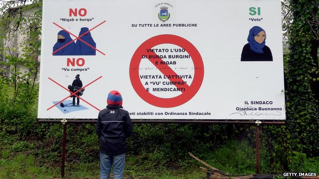 A young boy looks at a board on 30 April 2012 in Varallo, Italy, saying that the Burqa, Niqab and Burqini are not allowed in this city..