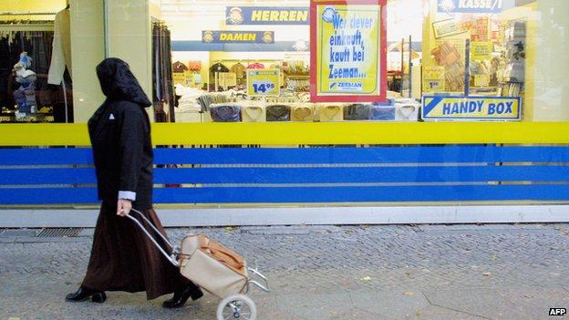 A Muslim woman passes a shop on 10 October 2001 in Berlin's heavily-Muslim Neukoelln district.