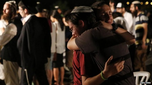 Jewish youths mourn beside the graves of the three dead teenagers 1 July 2014