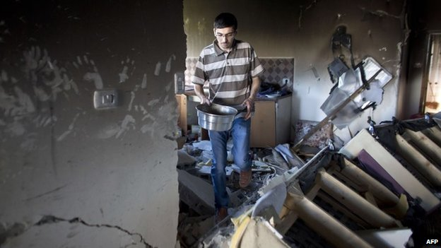 A relative inspects the damage to the house of Marwan Qawasmeh in the West Bank town of Hebron, 1 July 2014