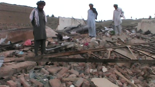 Local villagers look at destruction