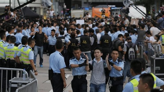A protester, front centre, is taken away by police officers after hundreds of protesters staged a peaceful sit-ins overnight on a street in the financial district in Hong Kong, 2 July 2014