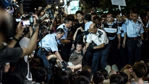 Policemen remove protesters in the central district after a pro-democracy rally seeking greater democracy in Hong Kong, 2 July 2014