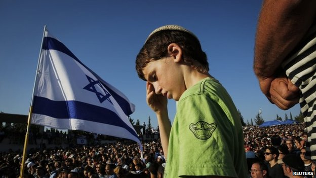 An Israeli boy attends the joint funeral of three Israeli teenagers in Modein, 1 July 2014