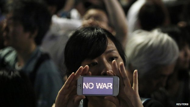 "A protester holds her smartphone displaying the phrase ""NO WAR"" at a rally against Japanese Prime Minister Shinzo Abe's push to expand Japan's military role in front of Abe's official residence in Tokyo on 1 July, 2014"