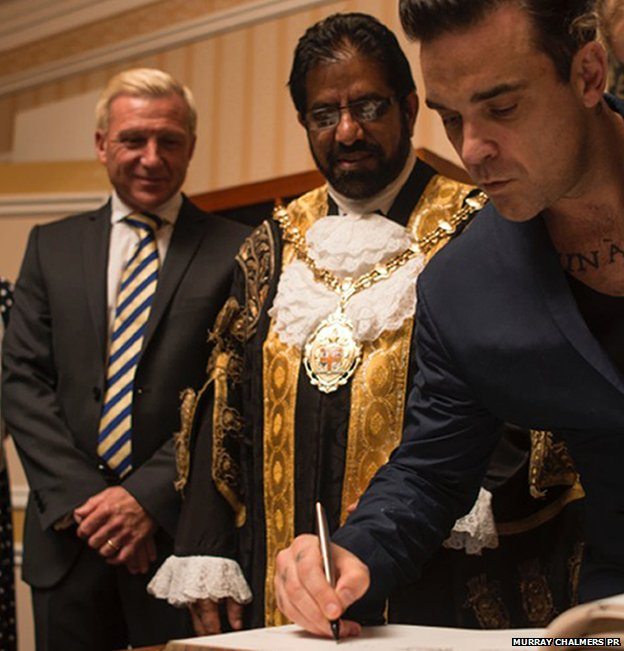 Robbie Williams signs the roll of honour