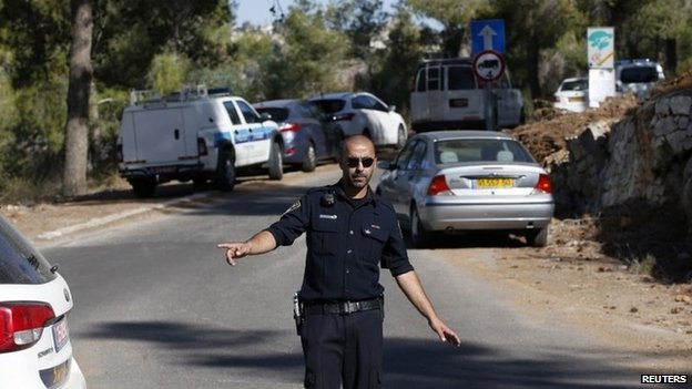 Israeli police officer gestures to journalists near the wood in Givat Shaul where the Palestinian teenager's body was found (2 July 2014)