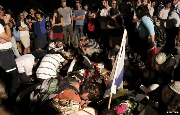 Mourners gather at the graves of the three murdered Israeli teenagers whose bodies were found in the West Bank on Monday (1 July 2014)