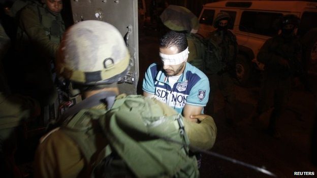 Israeli police detain a Palestinian in the city of Hebron on 2 July 2014
