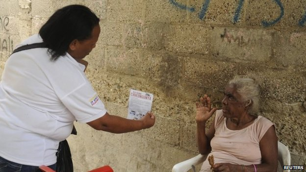 A health worker hands out a flyer about the Chikungunya virus in Santo Domingo on 23 May, 2014