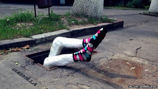Papier mache legs sticking out of pothole
