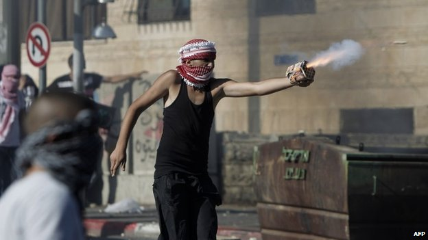 A Palestinian youth directs fireworks at Israeli riot police in East Jerusalem (2 July 2014)
