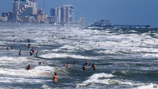 People deal with the high surf and currents off Daytona Beach, Florida, on 1 July 2014
