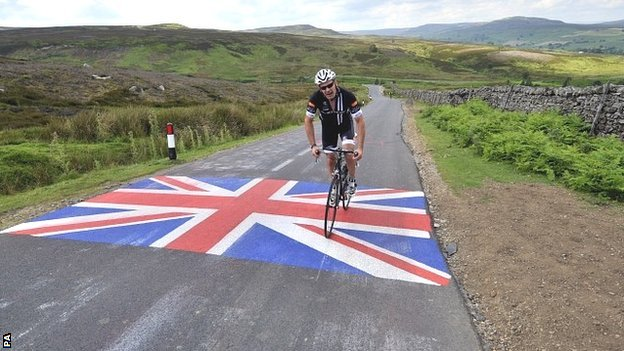 A rider passes over a Union flag painted on the road on the moors above Leyburn with the Yorkshire Dales in the background