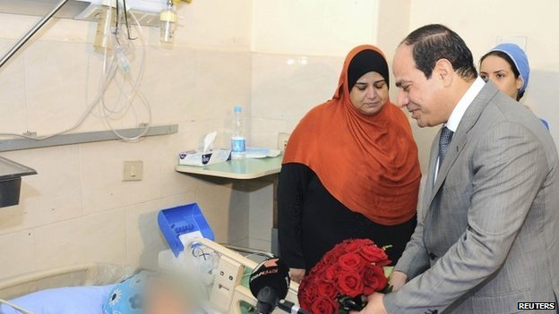 President Sisi presenting flowers to a woman who was sexually assaulted by a mob during his inauguration celebrations at a Cairo hospital on 11 June