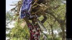 A displaced Nuer woman with a load of wood on her head in Bor, Jonglei State, South Sudan