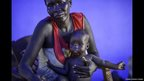 Elizabeth Akuol, a Dinka woman who fled Bor, pictured with one of her youngest child - Mingkaman, Lakes State, South Sudan