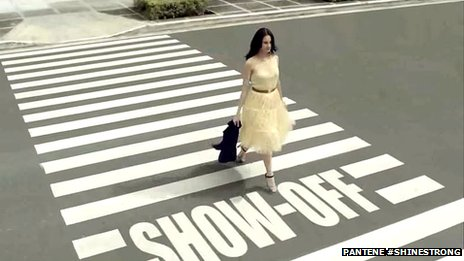 Woman walking across zebra crossing