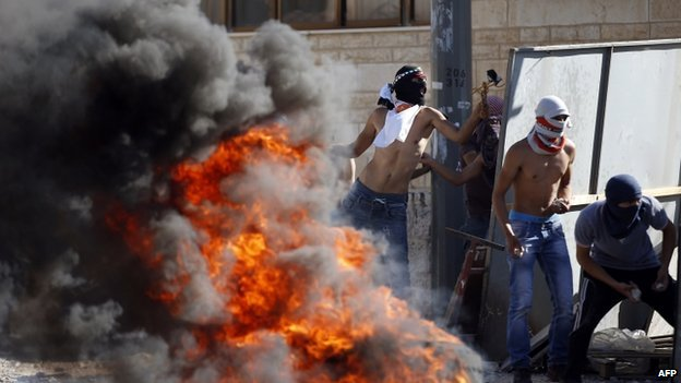 Masked Palestinian protesters throw stones at Israeli police during clashes in the Shuafat neighbourhood in East Jerusalem, on 2 July 2014,