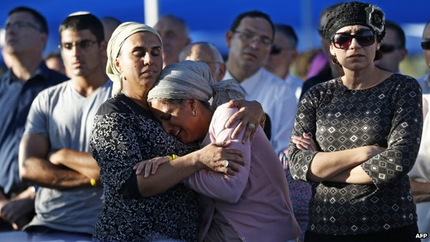 The mothers of two of the three Israeli teenagers killed in the West Bank mourn during the funeral of their sons on 1 July  2014 in the cemetery of Modiin in central Israel.
