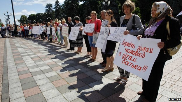 Relatives of men drafted into the army hold placards during a rally to demand their return during a rally near the Ukrainian parliament in Kiev on 2 July 2014.