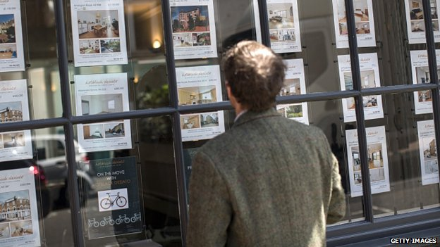 A man looks in an estate agent window