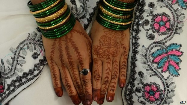 Mehendi (henna)-decorated hands of an Indian bride