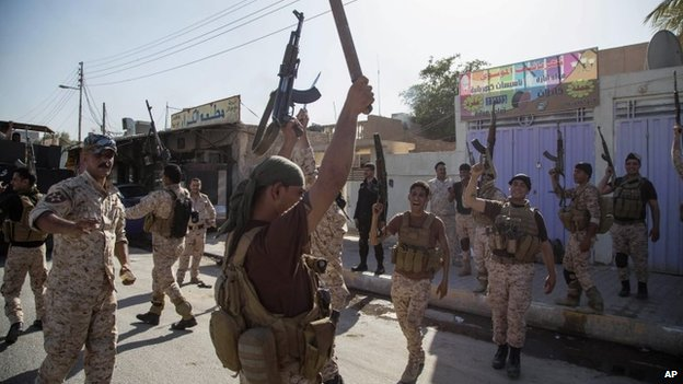 Iraqi soldiers celebrate following clashes with armed followers of Shia cleric Mahmoud al-Sarkhi in Karbala (2 July 2014)