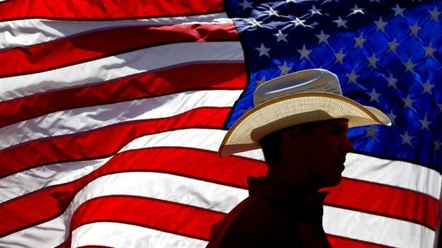 American wearing hat against US flag