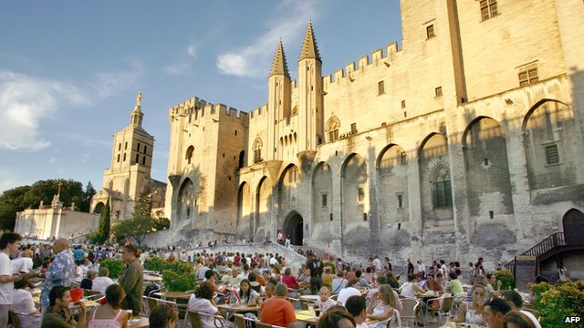 View of people sitting in cafes in front of the Papal Palace in Avignon in southern France