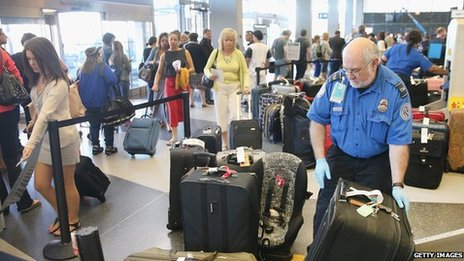A TSA agent checks luggage as passengers arrive for flights at O'Hare International Airport in Chicago, Illinois 23 May 2014