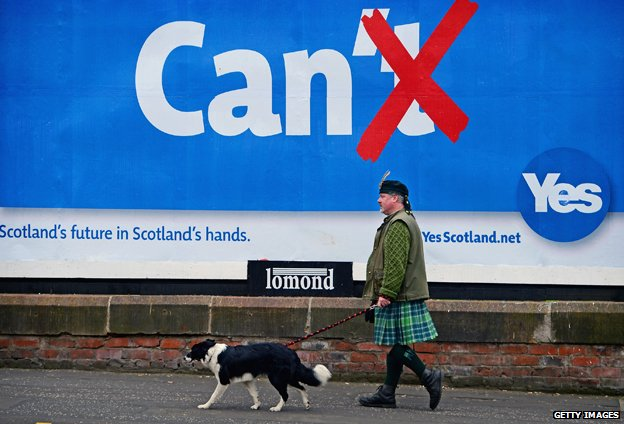 Colin MacDonald Provan ,walks his dog Colleen down Glasgow High Street past a Yes referendum campaign billboard On May 20, 2014
