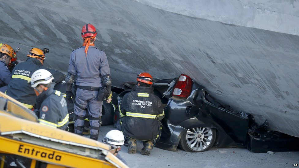 Fire department personnel work to retrieve a car from underneath a collapsed bridge in Belo Horizonte, Brazil, on 3 July2014.