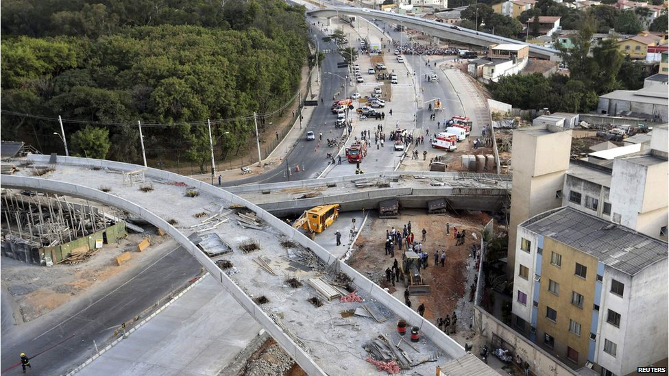 Rescue workers try to reach vehicles trapped underneath a bridge that collapsed while under construction in Belo Horizonte on 3 July 2014.