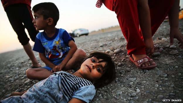 Iraqi children who fled fighting near Mosul prepare to sleep on the ground with their family in Khazair, Iraq. Photo: 3 July 2014