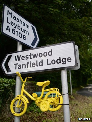 A miniature yellow bicycle hangs from road signs on the Tour De France route near North Stainley